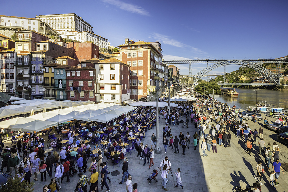 ourists at restaurants in the Ribeira riverside district of Porto with the old traditional bridge, the Dom Luis I bridge and a old buildings background, also queing up for traditional boat rides along the riverbanks. It is now a UNESCO World Heritage site.