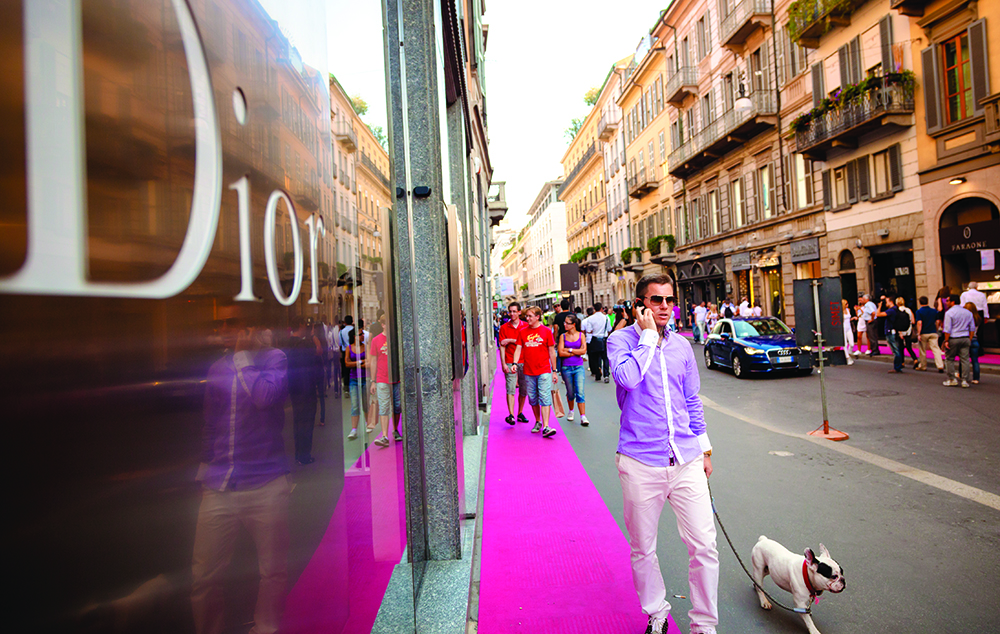 Man with dog walk past the road outside the Dior store at Via Montenapoleone Street, the high-class fashion shopping district. Dior is a luxury fashion brand famous for haute couture, fashion and accessories for men and women headquartered in Paris, France.""