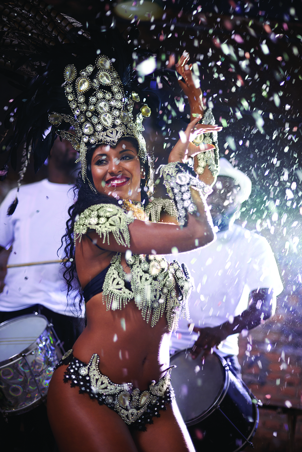 A beautiful samba dancer performing in a carnival with her band