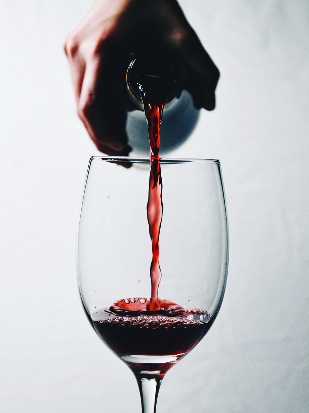 Close-Up Of Hand Pouring Wine Into Glass