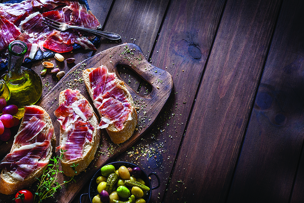 A rustic wooden table filled with delicious ingredients for preparing and eating Iberico ham sandwich known as Bocadillo de Jamón Iberico in Spain