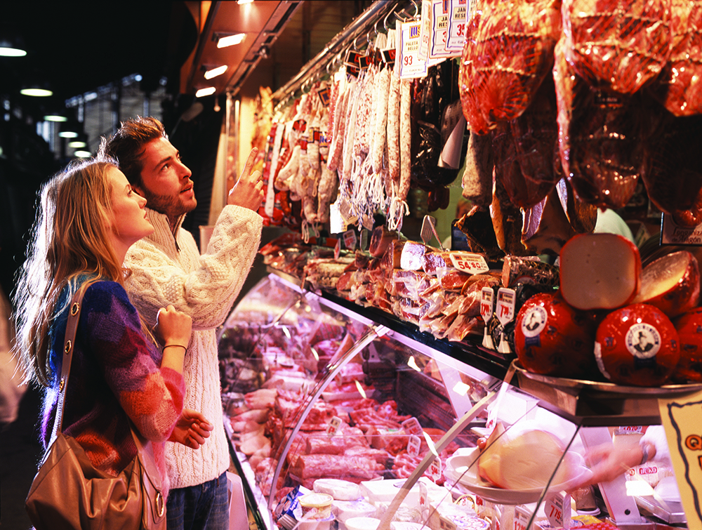 Young couple at meat counter in market in Barcelona, Spain