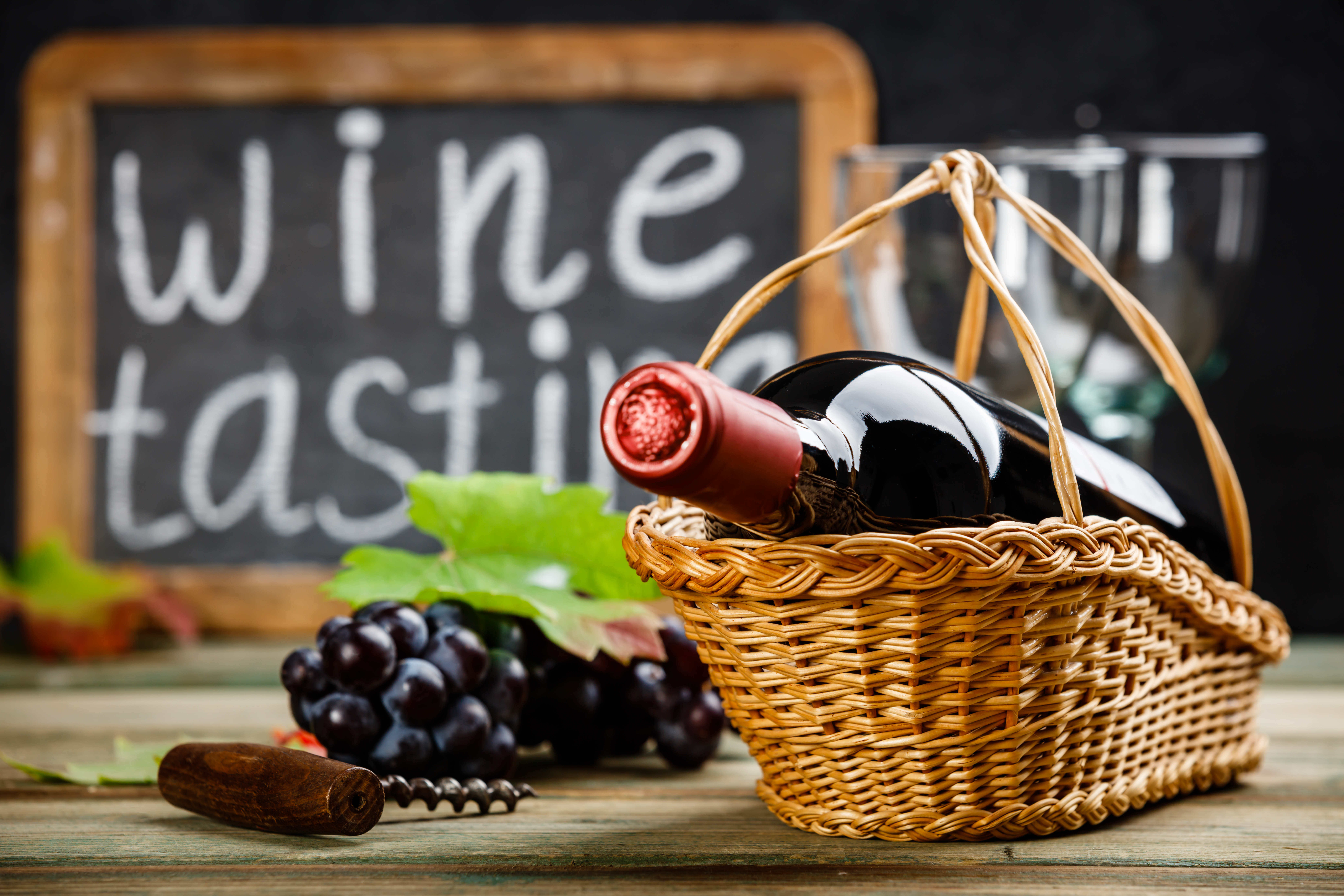 Wine tasting concept. Wine in basket with grapes, leaves and corks on dark background, copyspace