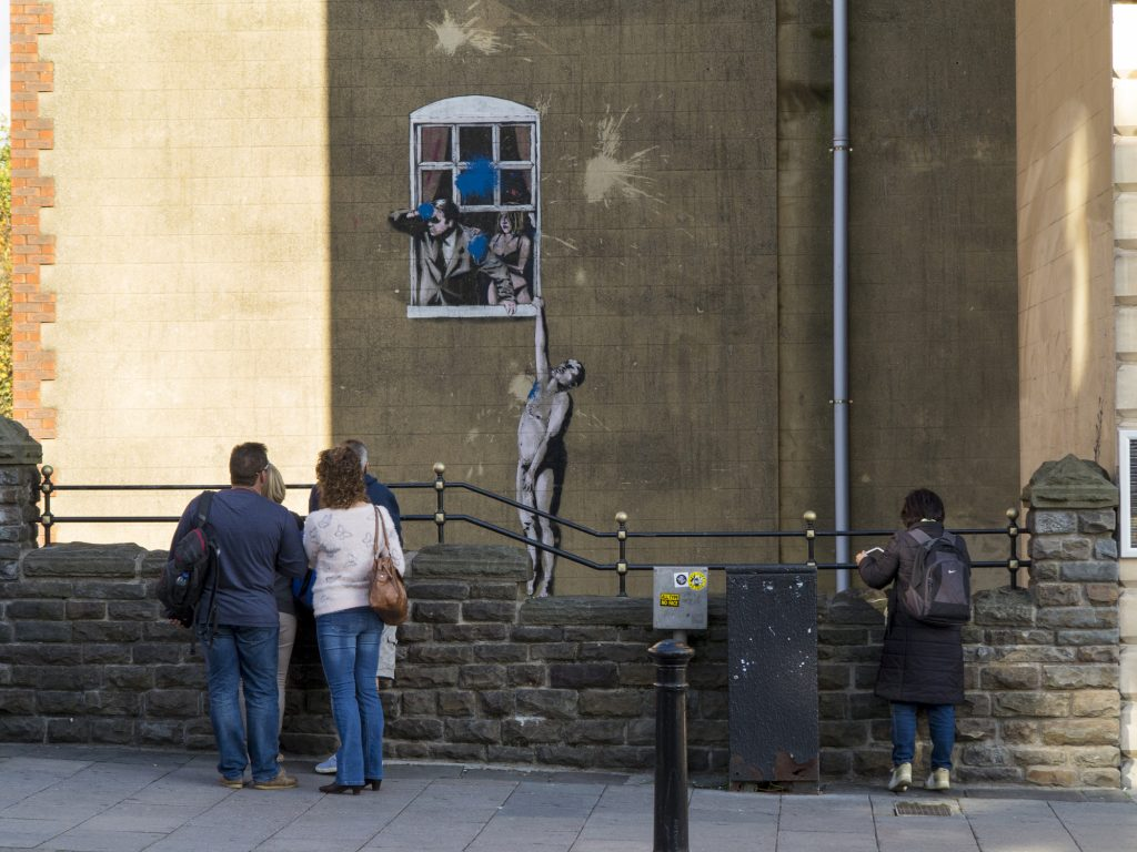 Bristol, UK - November 1, 2014: Viewed from Park Street, Naked Man - is an original example of Banksy grafitti artwork in Bristol which itself has been defaced by a paint bomb attack. It still attracts the attention of many visitors to Bristol.